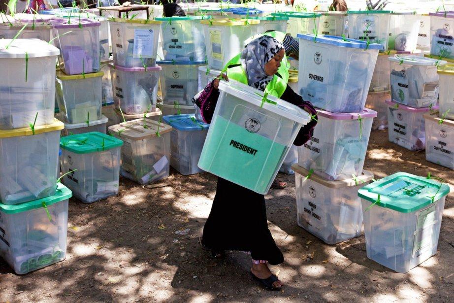 Une vérificatrice de l'IEBC transporte une boîte contenant... (PHOTO IVAN LIEMAN, AFP)
