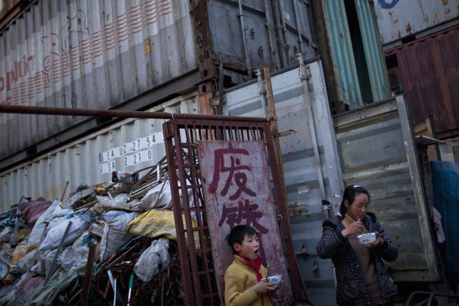 Une mère et sa fille prennent le repas à l'extérieur du conteneur qui leur sert de logement, à Shanghai, une habitation qui leur coûte 80$ par mois. | 5 mars 2013