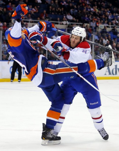 Brandon Prust (8) n'y va pas de main morte aux dépens de Travis Hamonic (3). (PHOTO PAUL J. BERESWILL, AP)