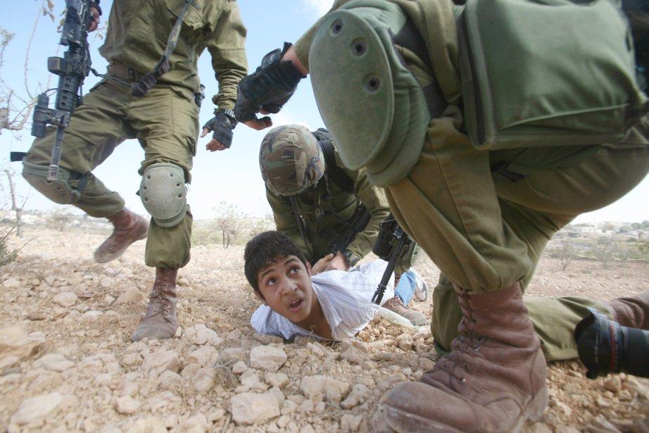 Un garçon palestinien est arrêté par des soldats... (PHOTO HAZEM BADER, ARCHIVES AFP)