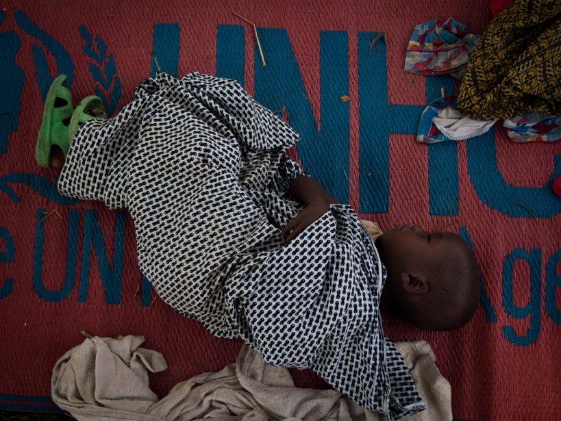 Un jeune enfant dort dans une couverture du UNHCR au camp de réfugiés de Rwamwanja dans l'ouest de l'Uganda, où habitent 35 000 réfugiés, la plupart venant du Congo. | 6 mars 2013