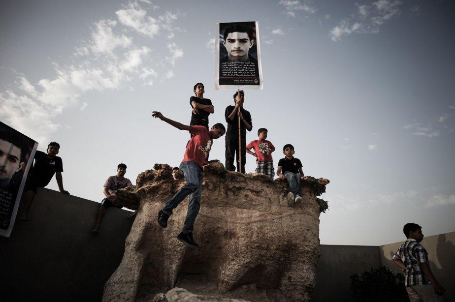 Des jeunes Bahreïnis tiennent une pancarte avec le portrait de Mahmoud al-Jaziri, lors de ses funérailles, au sud de Manama. | 6 mars 2013