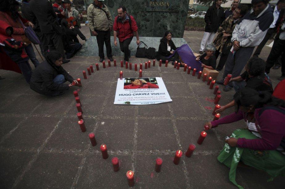 Plusieurs personnes se recueillent près de bougies disposées en forme de coeur autour d'une photographie d'Hugo Chavez, au Guatemala. | 7 mars 2013