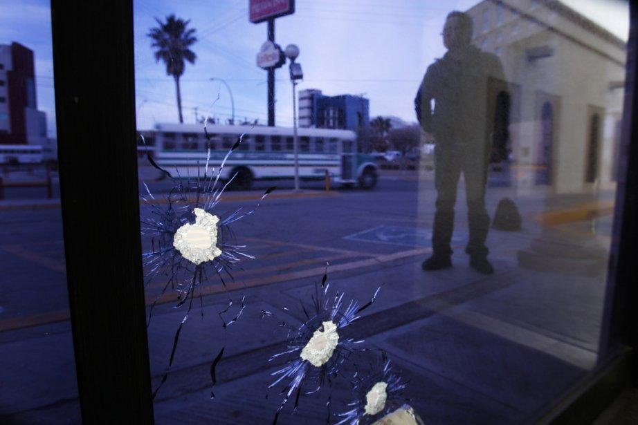Un homme se tient à proximité des fenêtres du journal El Diario, criblées de balles, à Ciudad Juarez. | 7 mars 2013