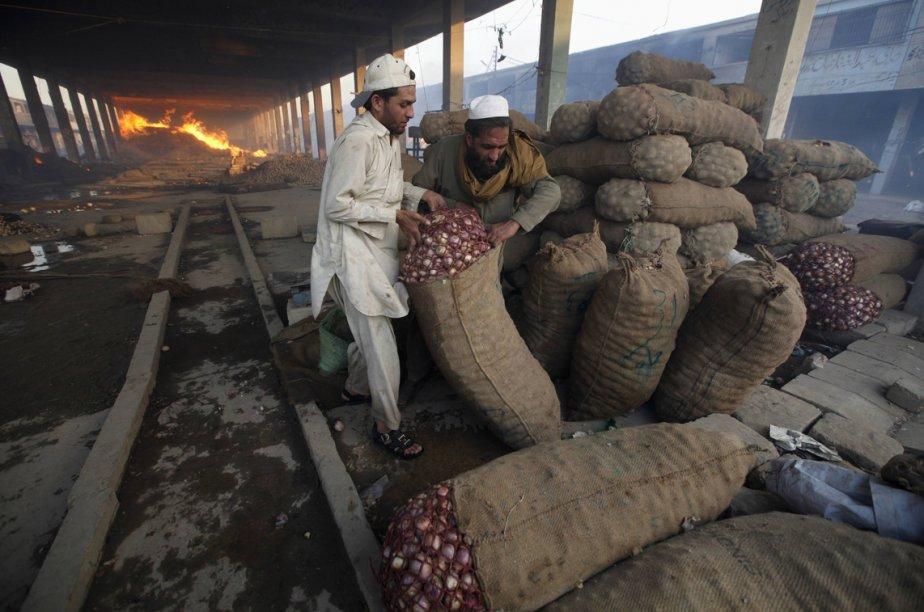 Des hommes déplacent des sacs d'oignons pour les entreposer dans un endroit plus sécuritaire, après un incendie dans un marché de fruits et légumes, en banlieue de Karachi. | 7 mars 2013
