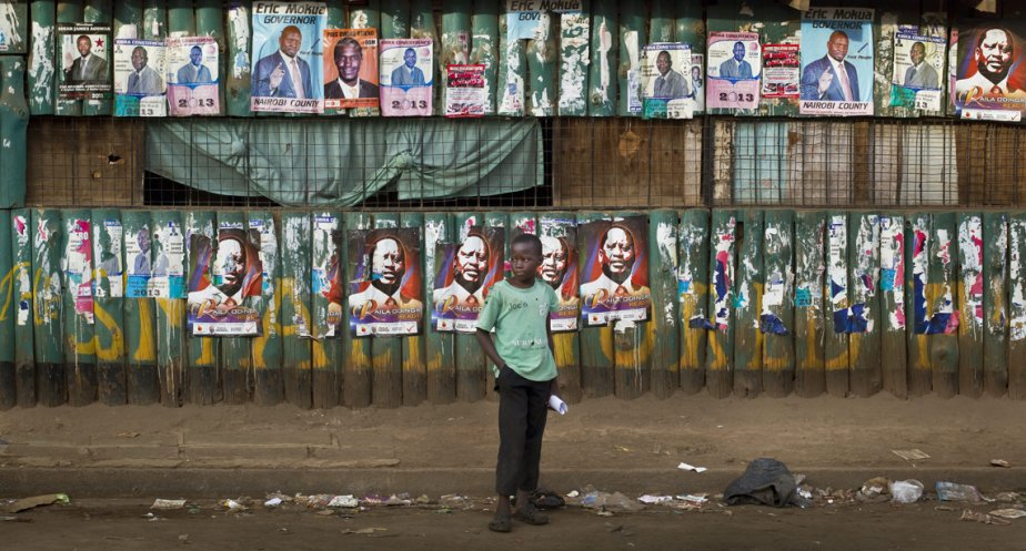 Un garçon se tient devant un mur tapissé d'affiches électorales, dans le bidonville de Kibera, à Nairobi. | 7 mars 2013