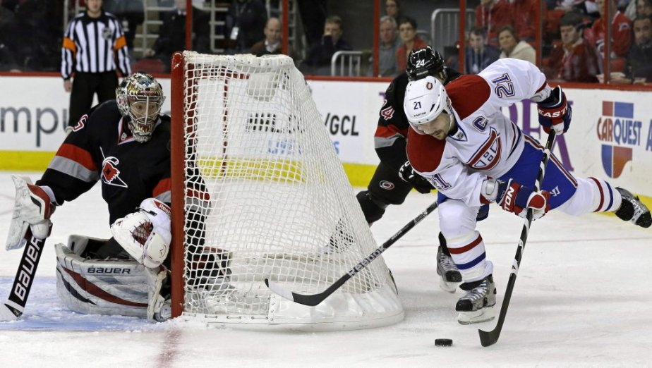 Brian Gionta derrière le filet de Justin Peters. (Photo Gerry Broome, Associated Press)