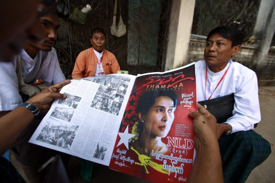 Des délégués lisent le journal où apparaît Suu... (PHOTO SOE ZEYA TUN, REUTERS)