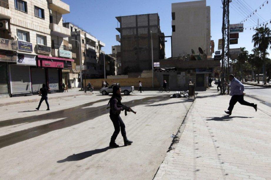 Un homme court pour se protéger lors d'un... (PHOTO Hamid Khatib, REUTERS)