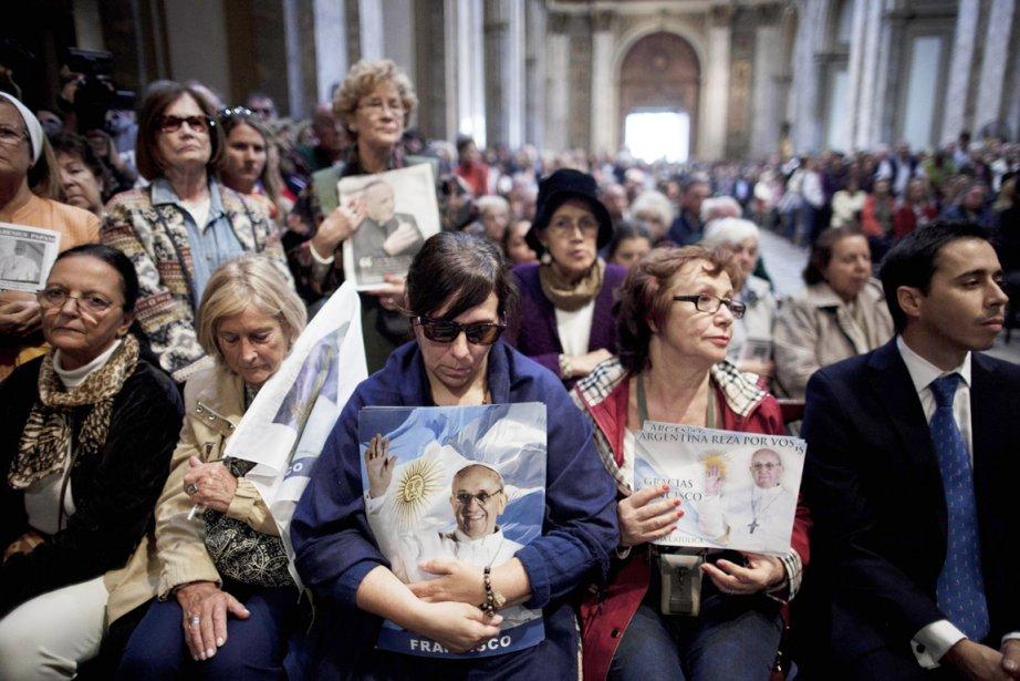 Des fidèles portant des images du pape François... (PHOTO NATACHA PISARENKO, AP)