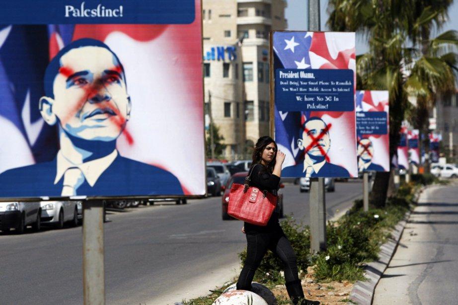 Une Palestienne passe devant des affiches vandalisées annonçant... (PHOTO MAJDI MOHAMMED, ARCHIVES AP)