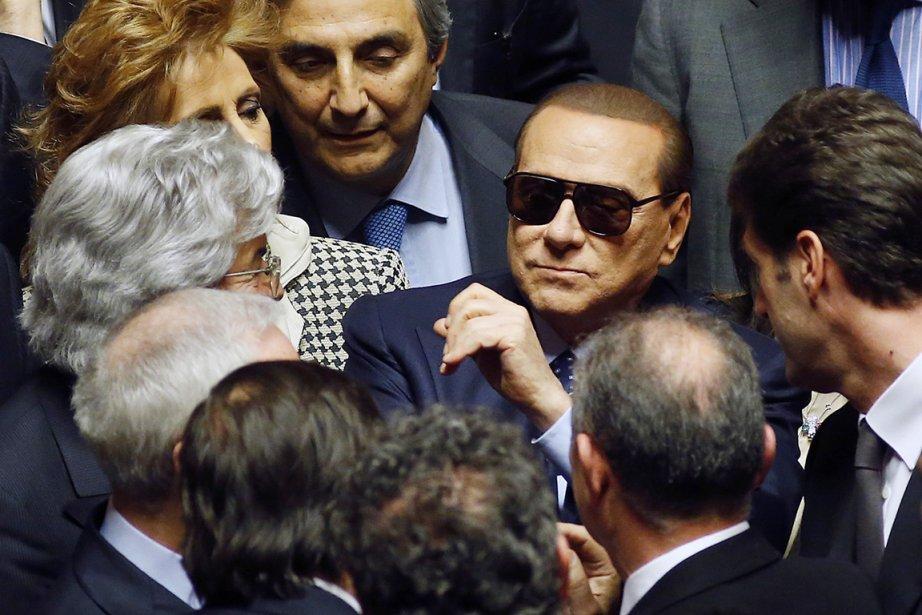 Silvio Berlusconi est entouré par ses collaborateurs à... (PHOTO REMO CASILLI, REUTERS)