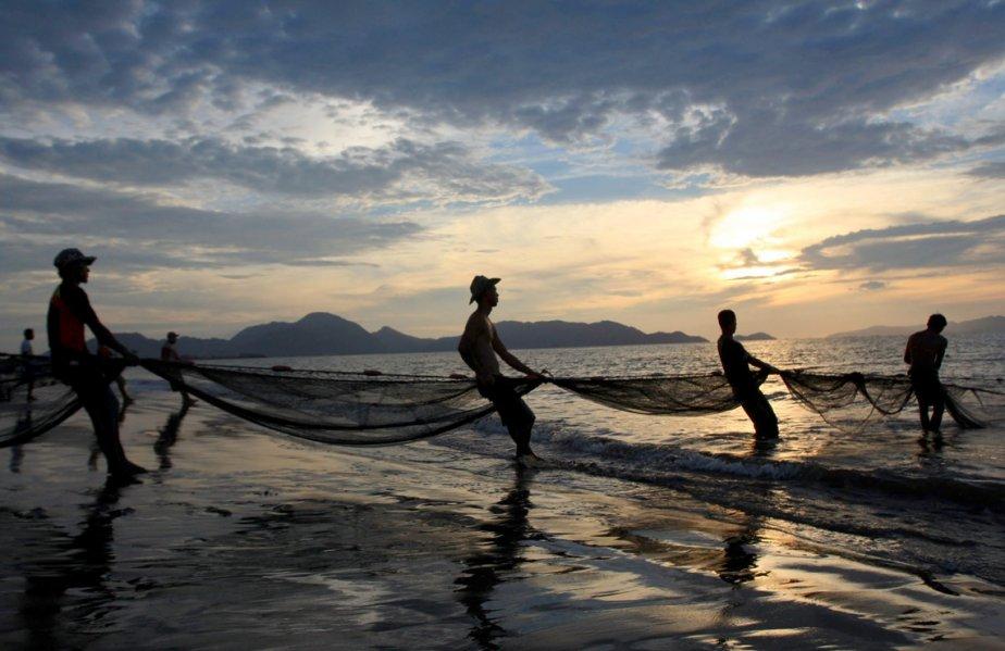 Des pêcheurs tirent un filet lors du coucher de soleil sur une plage de Banda Aceh en Indonésie. | 19 mars 2013