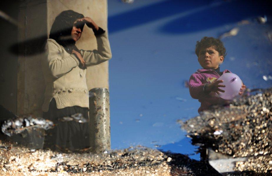 Le reflet de deux réfugiés syriens dans une flaque d'eau dans le camp de Bab al-Haqa, près de la frontière turque. | 19 mars 2013