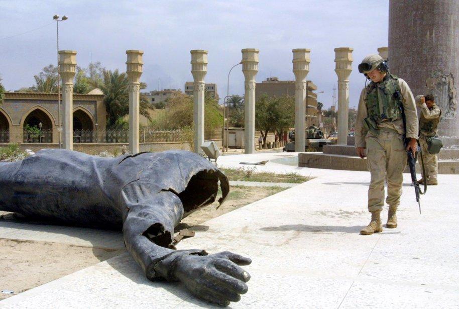 Un soldat américain regarde avec amusement une statue... (PHOTO PATRICK BAZ, AFP)