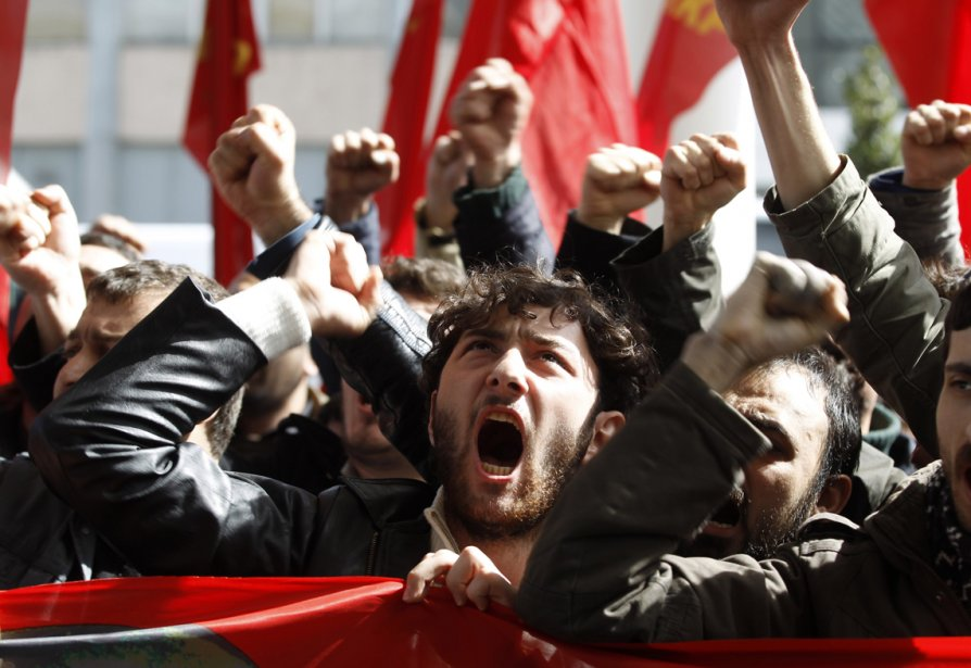 Des partisans turcs du Parti communiste crient des slogans lors d'une manifestation conte le Conseil national syrien (CNS) en face d'un hôtel d'Istanbul, où l'opposition syrienne tient une réunion. | 20 mars 2013
