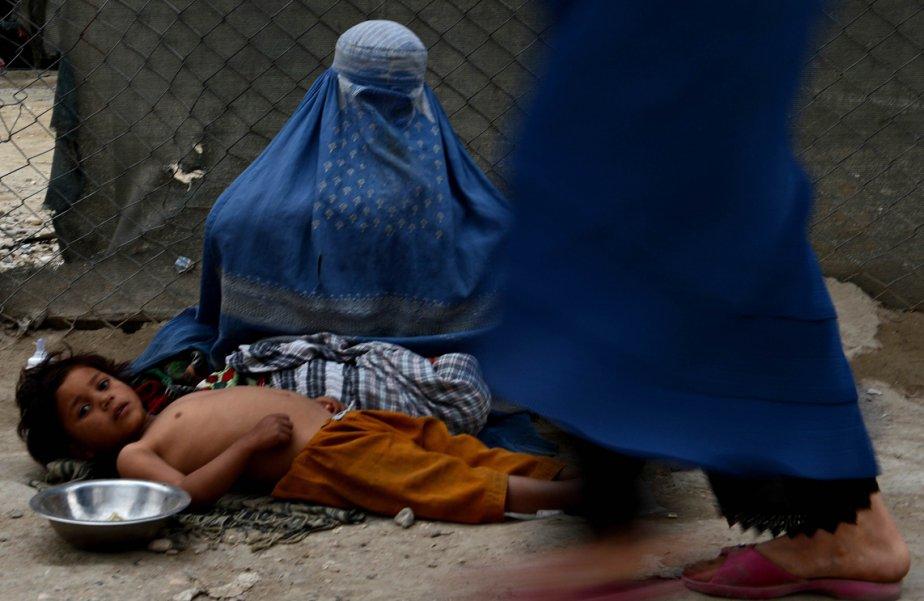 Une femme afghane mendie avec son enfant aux abords d'une route près du sanctuaire de Hazrat-i Ali. Quelques neuf millions d'Afghans, soit 36% de la population, vivent dans la