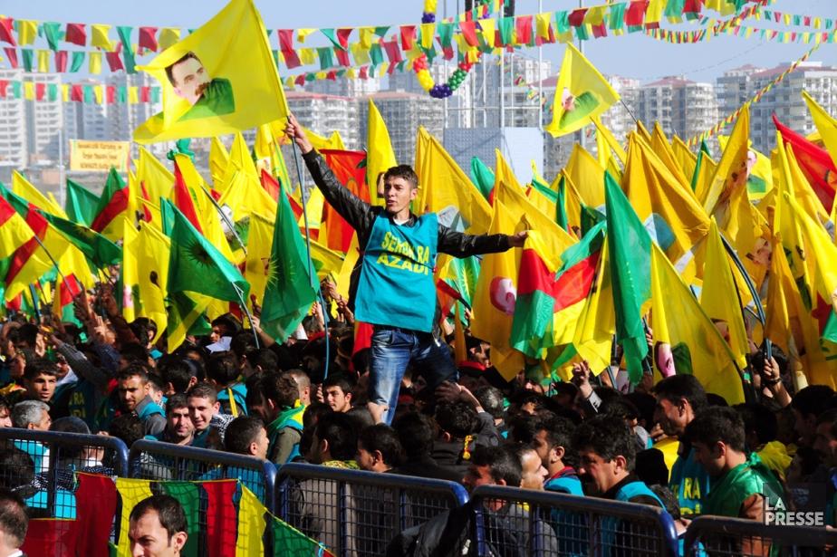 Un jeune Kurde agite un drapeau à l'effigie... (PHOTO AFP)
