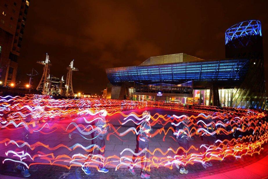 Des centaines de coureurs munis de lumières à l'extérieur du théâtre Lowry à Manchester en Angleterre. | 22 mars 2013