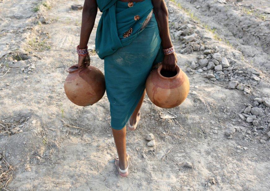 Une fermière indienne transporte une cruche d'eau à Allahabad pour irriguer des plants de concombres en cette Journée mondiale de l'eau. | 22 mars 2013