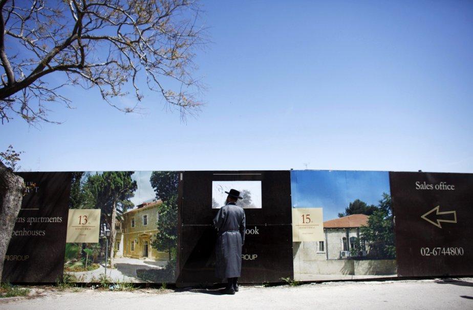 Un juif ultra-orthodoxe observe un site de construction par le trou d'un mur temporaire à Jérusalem, en Israël. | 22 mars 2013