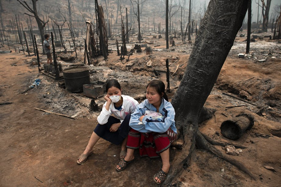 Des réfugiées birmanes attendent dans un camp incendié... (Photo: AFP)