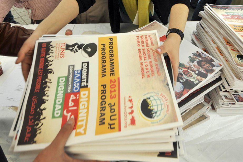 Des gens distribuent le programme du 10e Forum... (Photo: AFP)