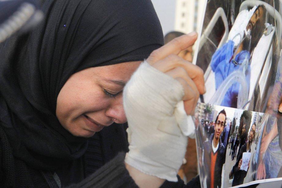 Une femme pleure alors qu'elle brandit un photomontage... (PHOTO AMR NABIL, AP)