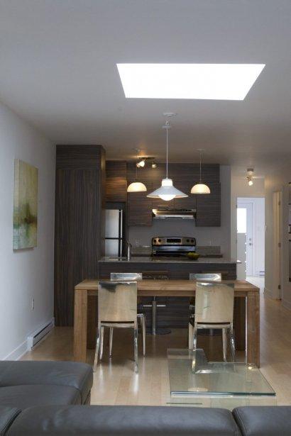 Le condo-témoin de deux chambres, d'une superficie de 814 pi2, est fidèle à la réalité. La cuisine est aménagée au coeur de l'appartement, afin de faire entrer le plus de lumière possible par les fenêtres du salon. La hotte en inox et les luminaires sont fournis. | 27 mars 2013