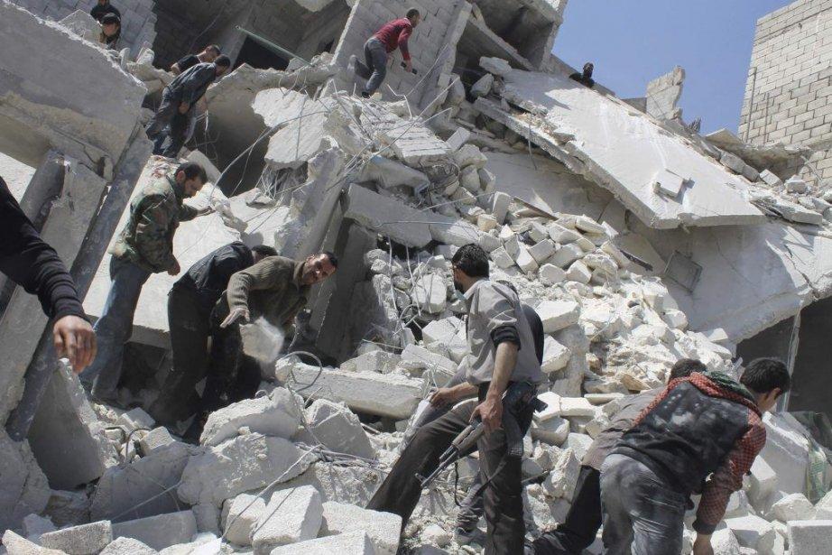 Des Syriens fouillent sous les décombres après le... (Photo Ziad Rev, REUTERS)