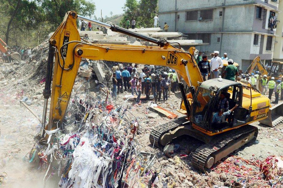 Les secouristes tentent à coups de pelle mécanique... (PHOTO PUNIT PARANJPE, AFP)