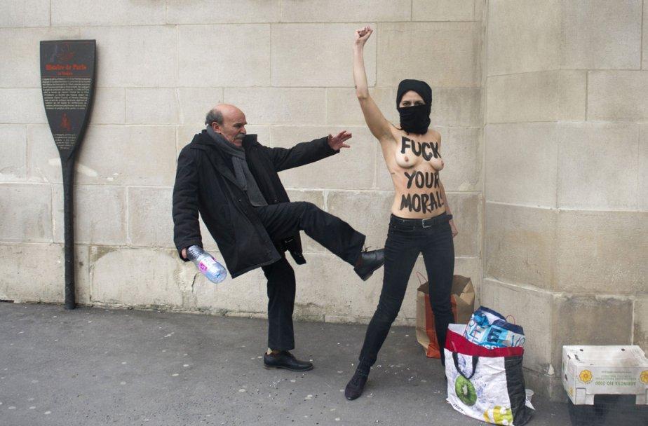 Un homme donne un coup de pied à une militante du mouvement féministe FEMEN lors d'une manifestation antiislamiste devant une mosquée de Paris. | 5 avril 2013