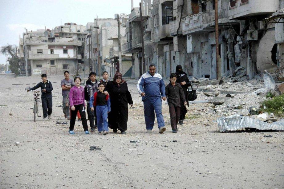 Des résidants de Homs marchent devant des bâtiments... (PHOTO SANA/REUTERS)