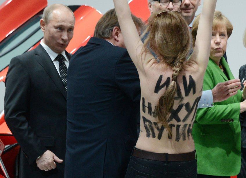 Le président russe Vladimir Poutine réagit à la présence d'une manifestante du mouvement féministe ukrainien FEMEN lors d'une foire industrielle à Hanovre en Allemagne. | 12 avril 2013