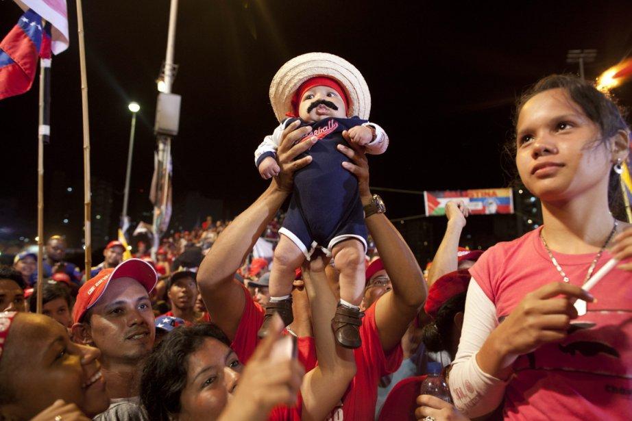 Un bébé portant la moustache du président du Venezuela, Nicolas Maduro, est porté à bout de bras lors d'un rassemblement à Caracas | 12 avril 2013