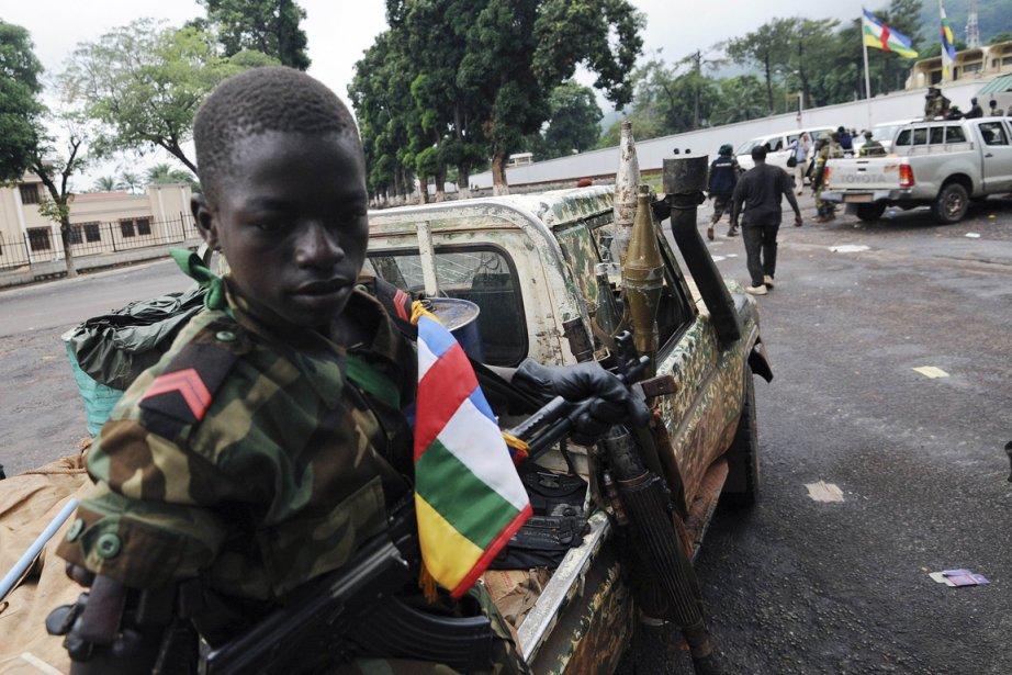 Unenfant soldat est assis dans un camion près... (PHOTO SIA KAMBOU, AFP)