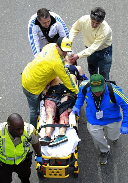 Medical workers aid an injured man at the finish line of the 2013 Boston Marathon following an explosion in Boston, Monday, April 15, 2013. Two bombs exploded near the finish of the Boston Marathon on Monday, killing two people, injuring 22 others and sending authorities rushing to aid wounded spectators, race organizers and police said. (AP Photo/Charles Krupa) | 15 avril 2013