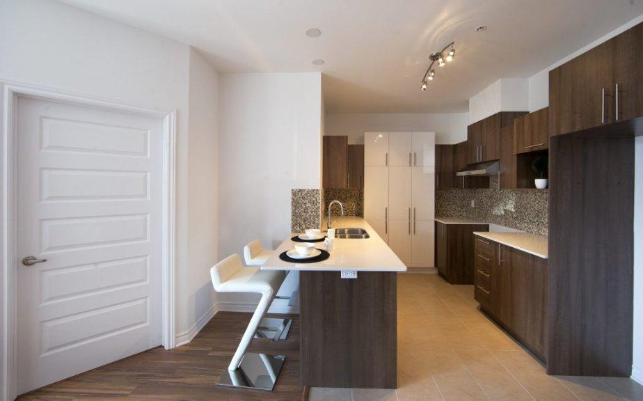 Il y a beaucoup d'espace de rangement dans la cuisine. Les plans de travail en quartz, l'évier encastré et la hotte en inox sont inclus dans le prix de vente. | 17 avril 2013