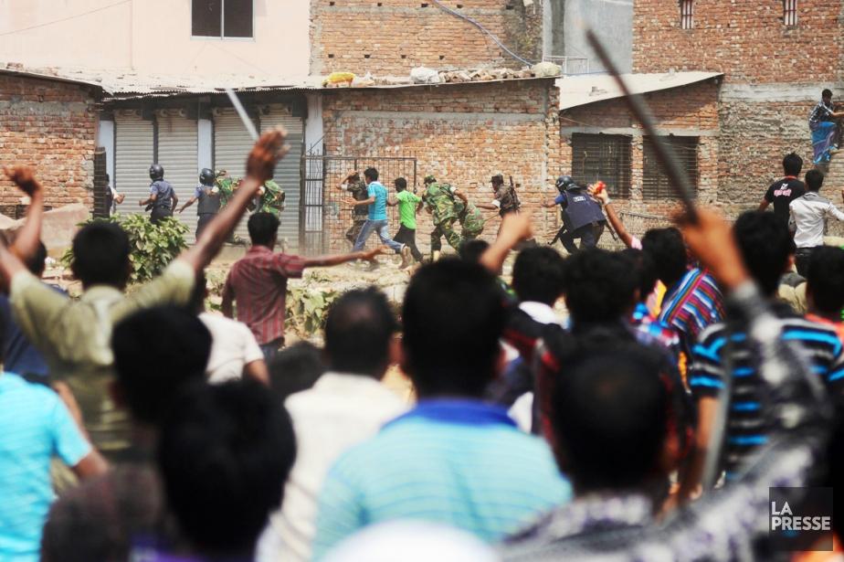 Des policiers et des soldats bangladais se sauvent... (PHOTO MUNIR UZ ZAMAN, AFP)