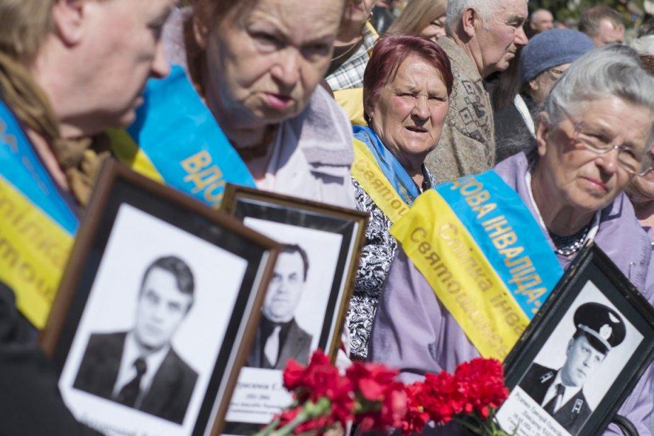 Des femmes tiennent des portraits de leurs proches... (PHOTO GLEB GARANICH, REUTERS)