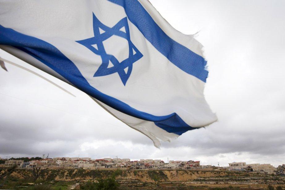Un drapeau israélien flotte sur une colline surplombant... (PHOTO RONEN ZVULUN, REUTERS)