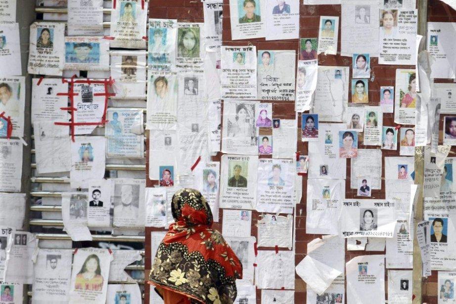 Une femme regarde un mur où sont affichées... (PHOTO ASHRAFUL ALAM TITO, AFP)