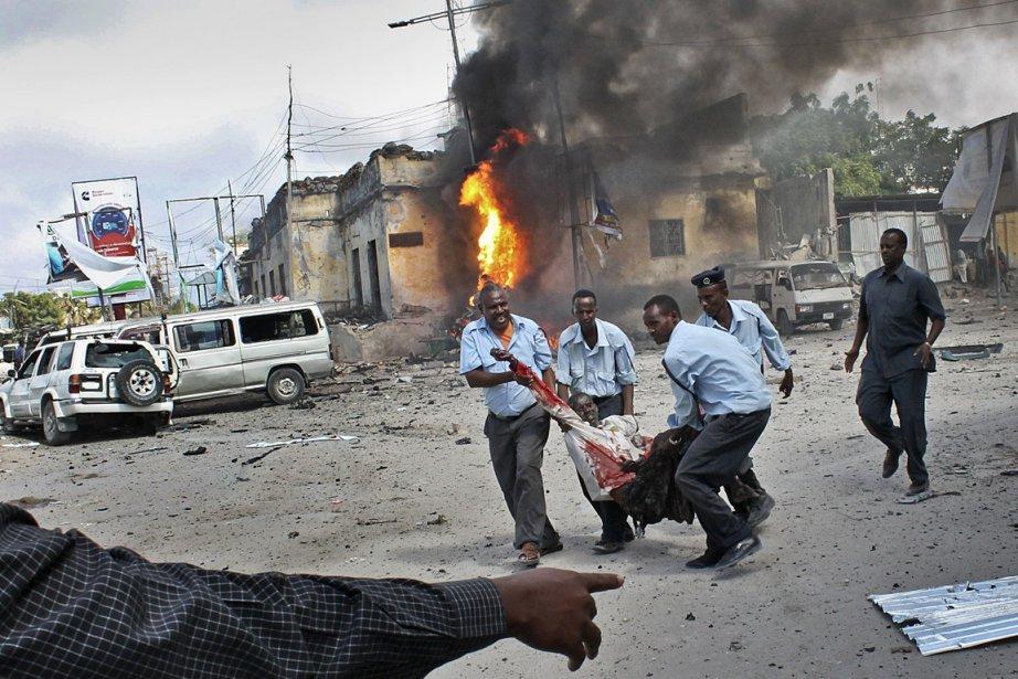 Des hommes portent une victime blessée par l'attentat... (Photo: AP)