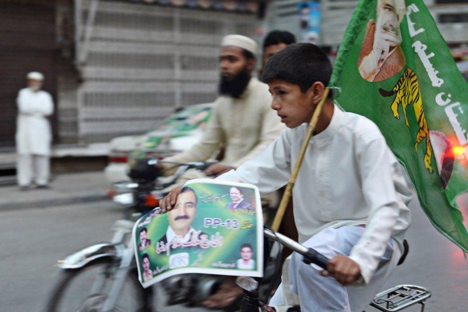 Un jeune pakistanais tient un drapeau et une... (PHOTO FAROOQ NAEEM, AFP)