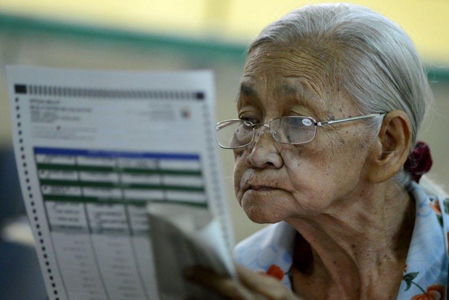 Une électrice philippine étudie son bulletin de vote.... (PHOTO NOEL CELIS, AFP)