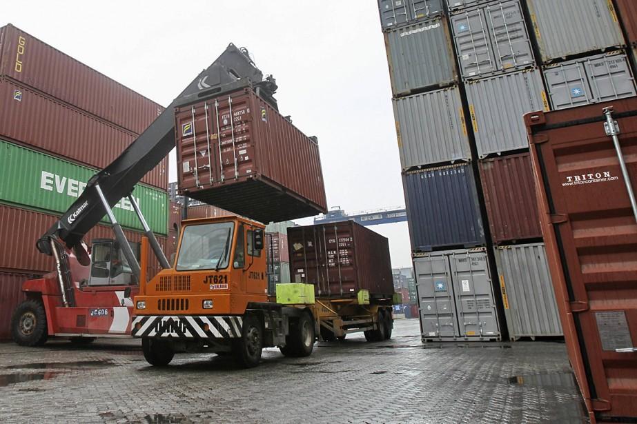 Un travailleur déplace des conteneurs à un port... (PHOTO ARCHIVES REUTERS)