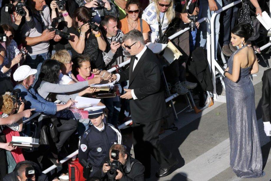 L'acteur Alec Baldwin signe des autographes, tandis que sa femme Hilaria Thomas l'attend.  Baldwin joue dans le film Blood Ties, qui était présenté ce lundi, hors compétition. | 20 mai 2013