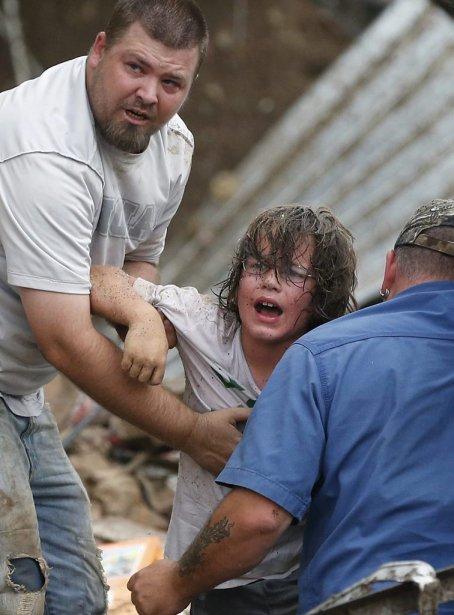 Un enfant appelle son père, après avoir été extrait des décombres, à Moore. (Photo Sue Ogrocki, AP)