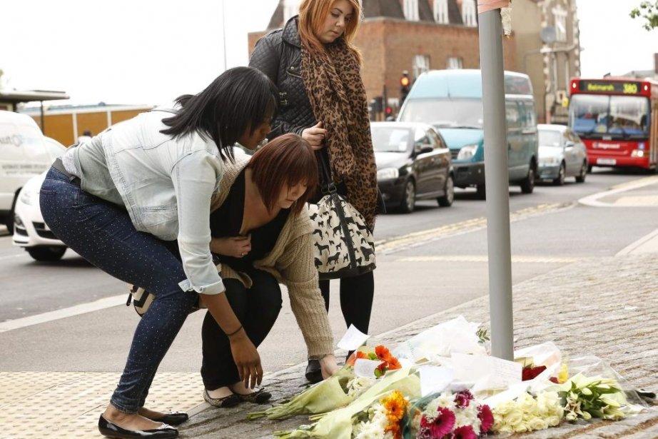 Des passantes déposent des fleurs proche du lieu... (Photo Reuters)