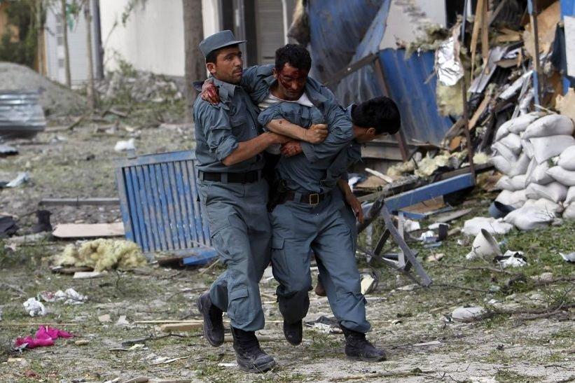 Un policier blessé est évacué du site de... (PHOTO OMAR SOBHANI, REUTERS)